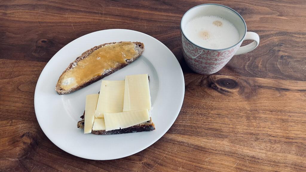 Das Bild zeigt einen Frühstücksteller mit einem Käsebrot und einem Honigbvrot und daneben einem Becher mit Milchkaffe.